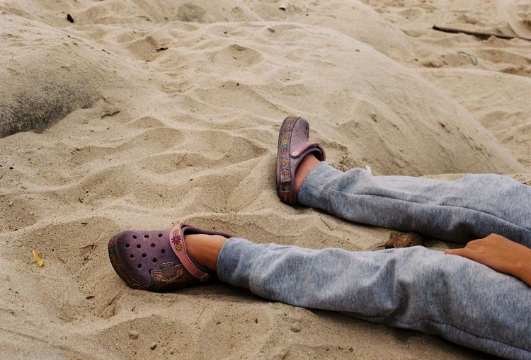 Low section of person lying on sand