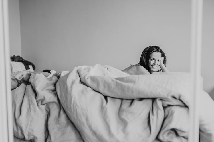 Portrait of smiling woman lying on bed against wall at home