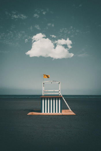 Lifeguard hut at beach against blue sky