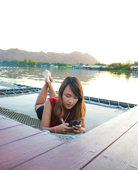 Woman using phone while lying on net by lake