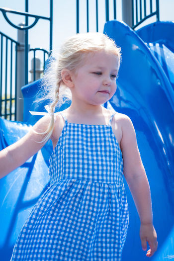 Close-up of girl looking away while standing against slide at playground