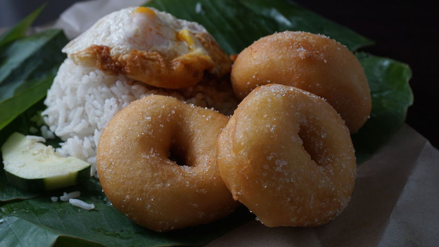 Close-Up Of Donuts And Rice On Banana Leaf