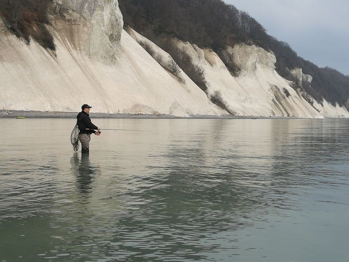 Side view of man fishing in lake against mountain