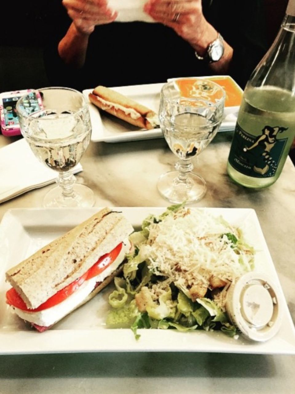 food and drink, human hand, food, plate, table, drinking glass, human body part, two people, bread, holding, healthy eating, drink, ready-to-eat, indoors, close-up, wineglass, sandwich, freshness, adult, adults only, people, day
