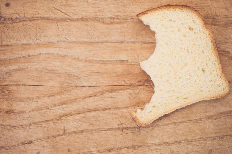 High angle view of bread slice on wooden table