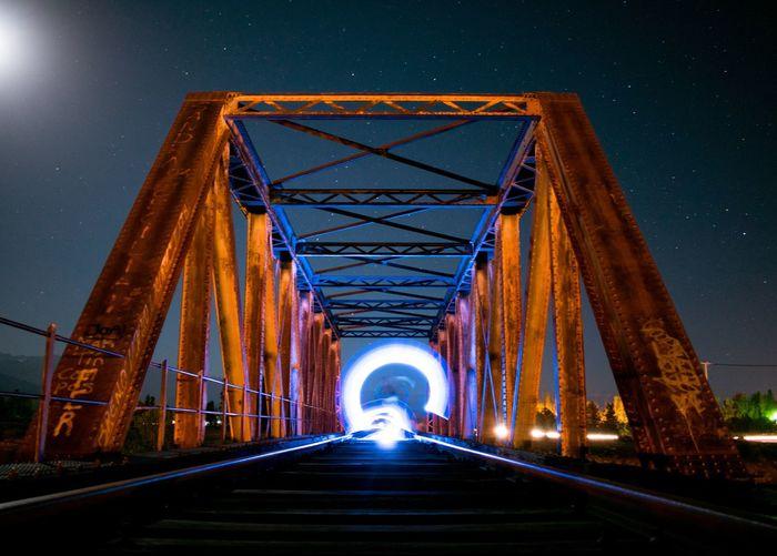 Bridge over road against sky at night