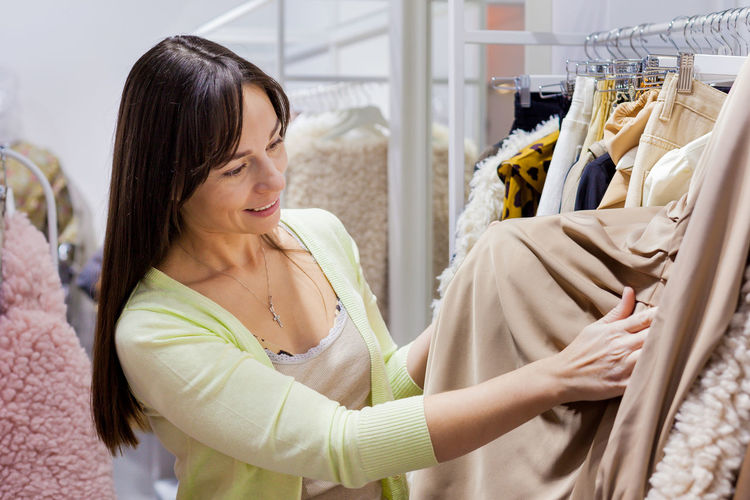 Smiling woman standing in clothing store