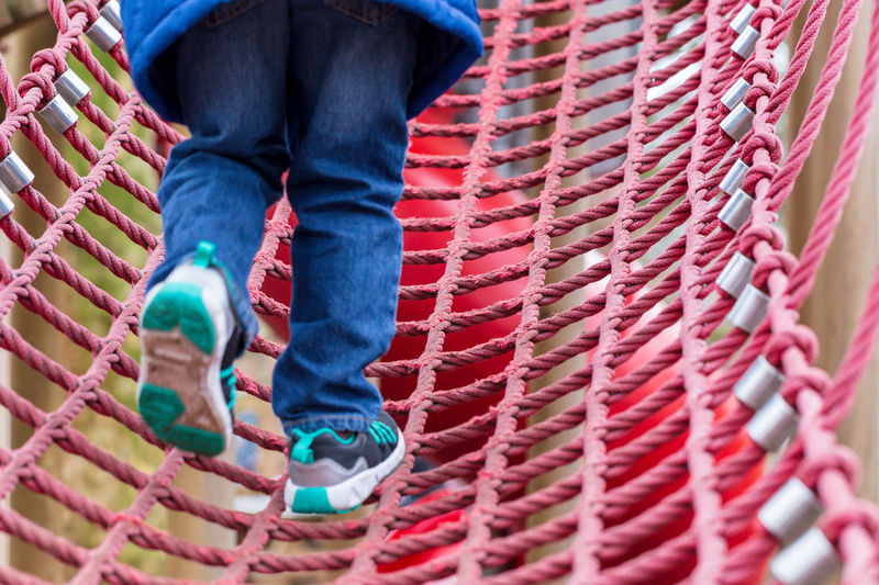 Low section of child climbing on rope bridge