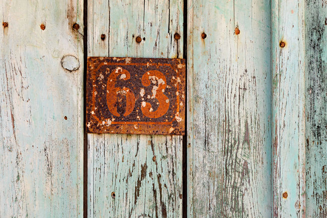 Rusty grunge metal house number plaque 63 on an old wooden door Number Of The House 63 House Number On Gate Paint Beauty In Decay Closeup Cracked Peeling Decayed Beauty Grunge Grungy House Number Plaque House Number Plate Metal Number Numbers Old Oxidation Patina Peeling Paint Plate Number Rusting Rusty Rusty Metal Vintage Wooden Door