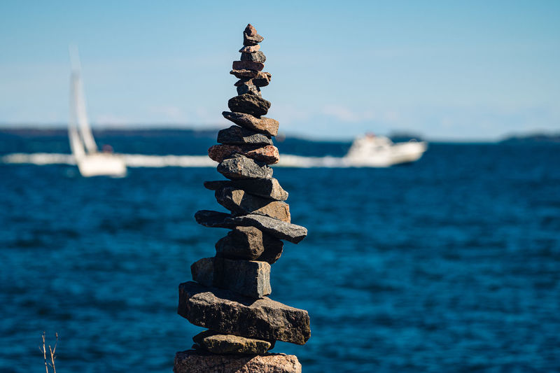 A closeup of a manmade pile of rocks against the blue sea with two boat sailing on the horizon.