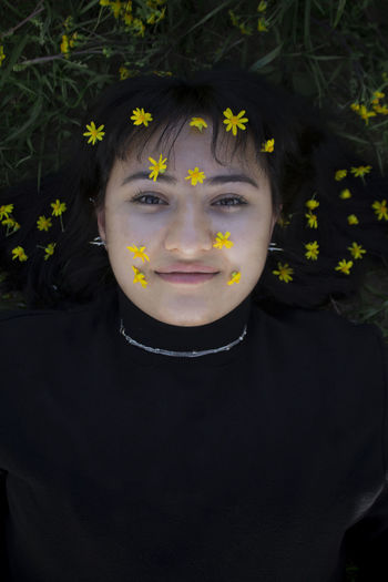 Woman wearing flowers while lying on grass
