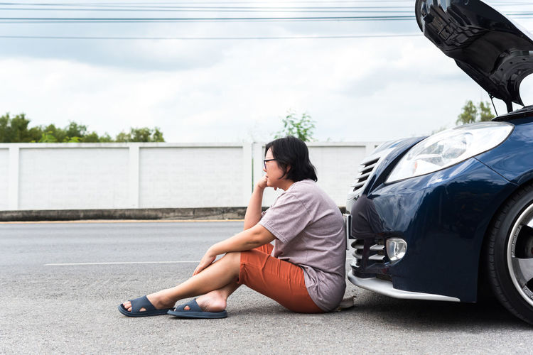 Side view of woman sitting on road by breakdown car against sky