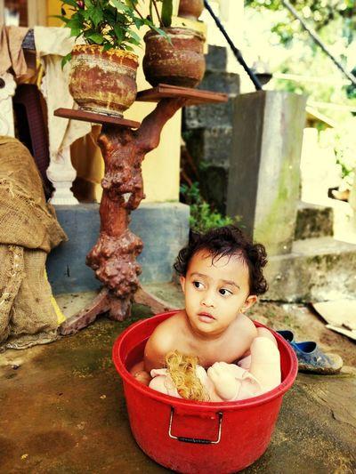 Cute Boy With Toy Sitting In Bath Tub