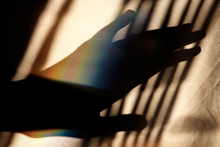 Close-up of silhouette hand by curtain