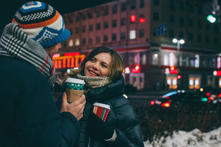 Young man and woman in illuminated city at night during winter