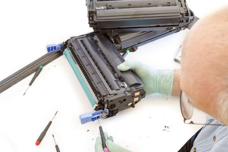 Cropped Image Of Person Repairing Machinery At Table