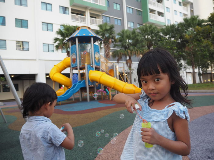 Portrait Of Cute Girl With Bubble Wand Standing By Sibling In Playground