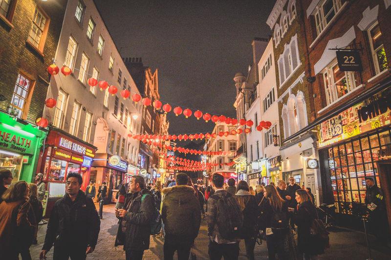 People walking on illuminated street in city at night