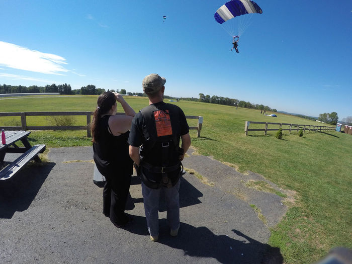 Couple Watching Skydivers Adventure Clear Sky Jumping Landscape Leisure Activity Lifestyles Nature Outdoors Parachute Parachuting People Real People Rear View Sky Skydiving Sport Two People