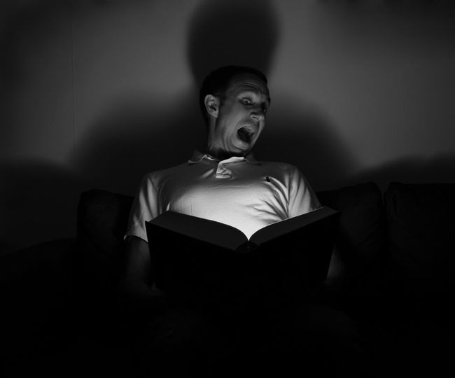 Man Making Face While Reading Book In Darkroom