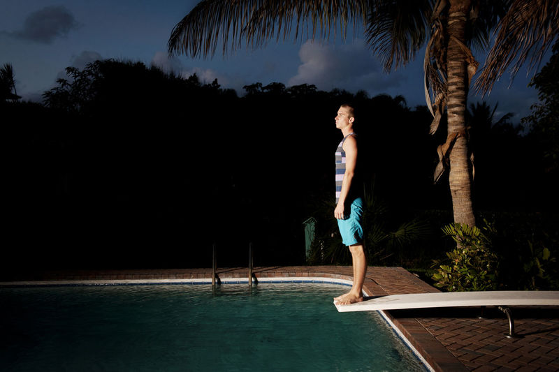 Man standing by swimming pool against sky