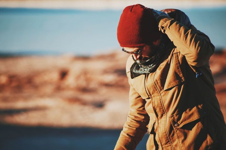 Close-Up Of Man In Warm Clothing At Beach On Sunny Day