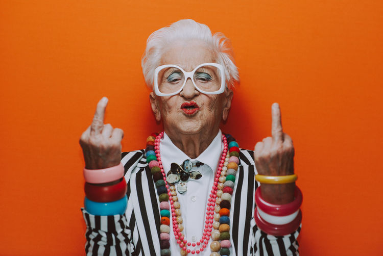 Portrait of senior woman wearing showing obscene gesture against red background