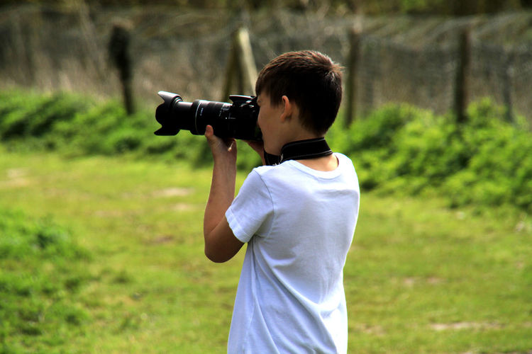 Boy Photographing On Grassy Field
