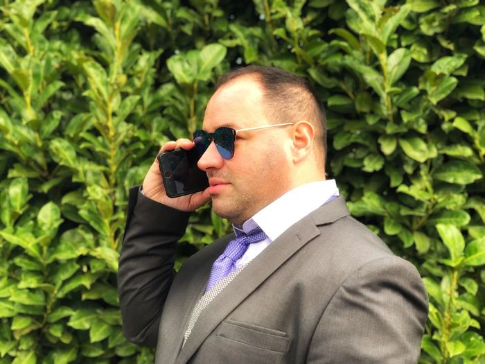 Businessman In Sunglasses Talking On Mobile Phone Against Plants