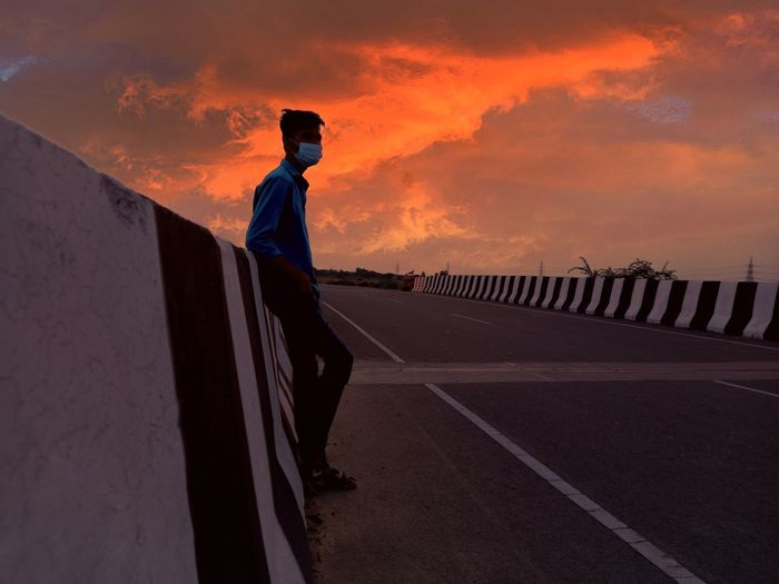 Man standing on road against sky during sunset