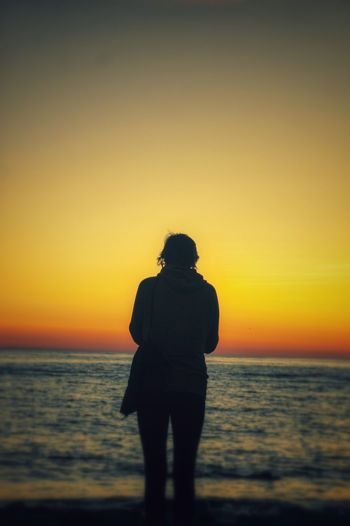 Rear view of silhouette young woman standing on beach during sunset