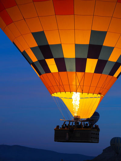 Hot air balloon flying against sky at sunset