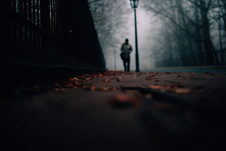 Surface level of man walking on footpath during foggy weather