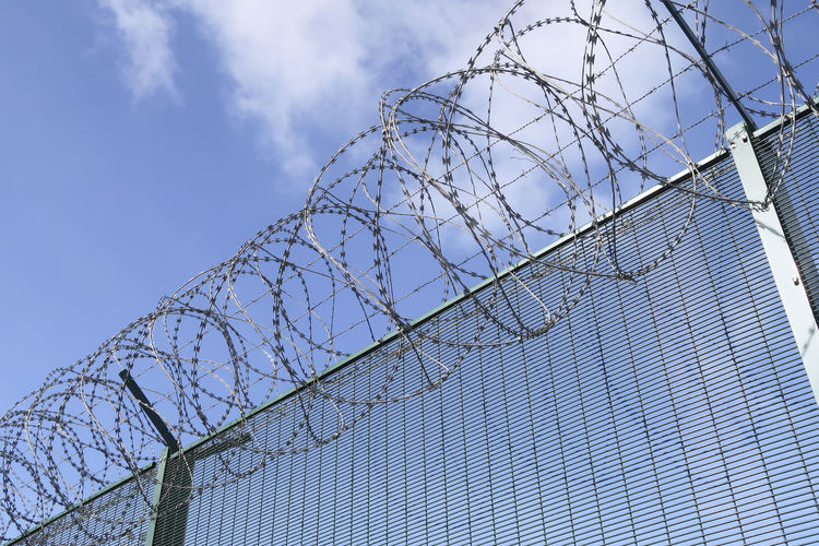 Part of a barbwired fence on a blue sky with clouds from a low angle view Barbed Wire Blue Border Boundary Chainlink Fence Close-up Cloud - Sky Day Fence Low Angle View Metal No People Outdoors Prison Prisoner Protection Razor Wire Restricted Area Safety Security Security System Sky