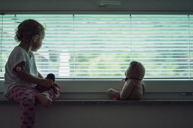 Rear view of girl sitting on toy against window