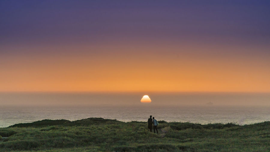 Observers of a distorted star Clear Sky Grass Landscape Nature Outdoors People Scenics Sea Sky Sun Sunset Tranquil Scene
