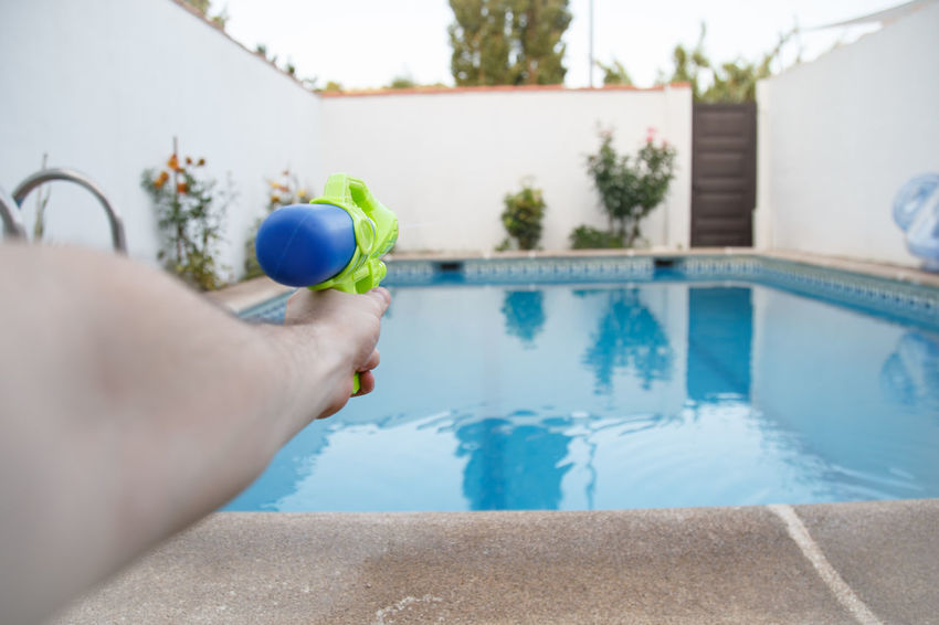 Crop shot of hand holding colorful water gun and aiming on background of pool in backyard. Aiming Anonymous Holidays Target Weekend Active Activity Body Part Enjoyment Entertainment Game Garden Leisure Games One Person Outdoors Playing Pointing Pool Poolside Recreational  Refreshing Shooting Summer Vacation Water Gun