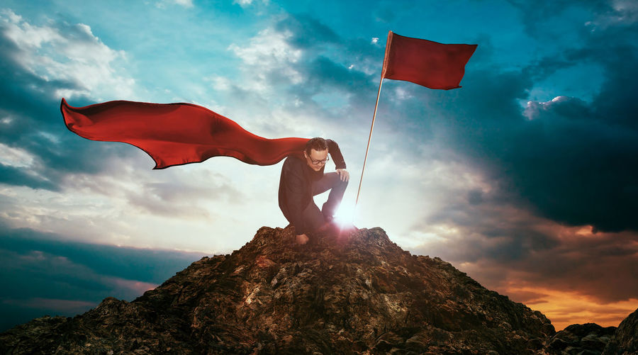 Low angle view of man in superhero costume kneeling by red flag on rock against sky