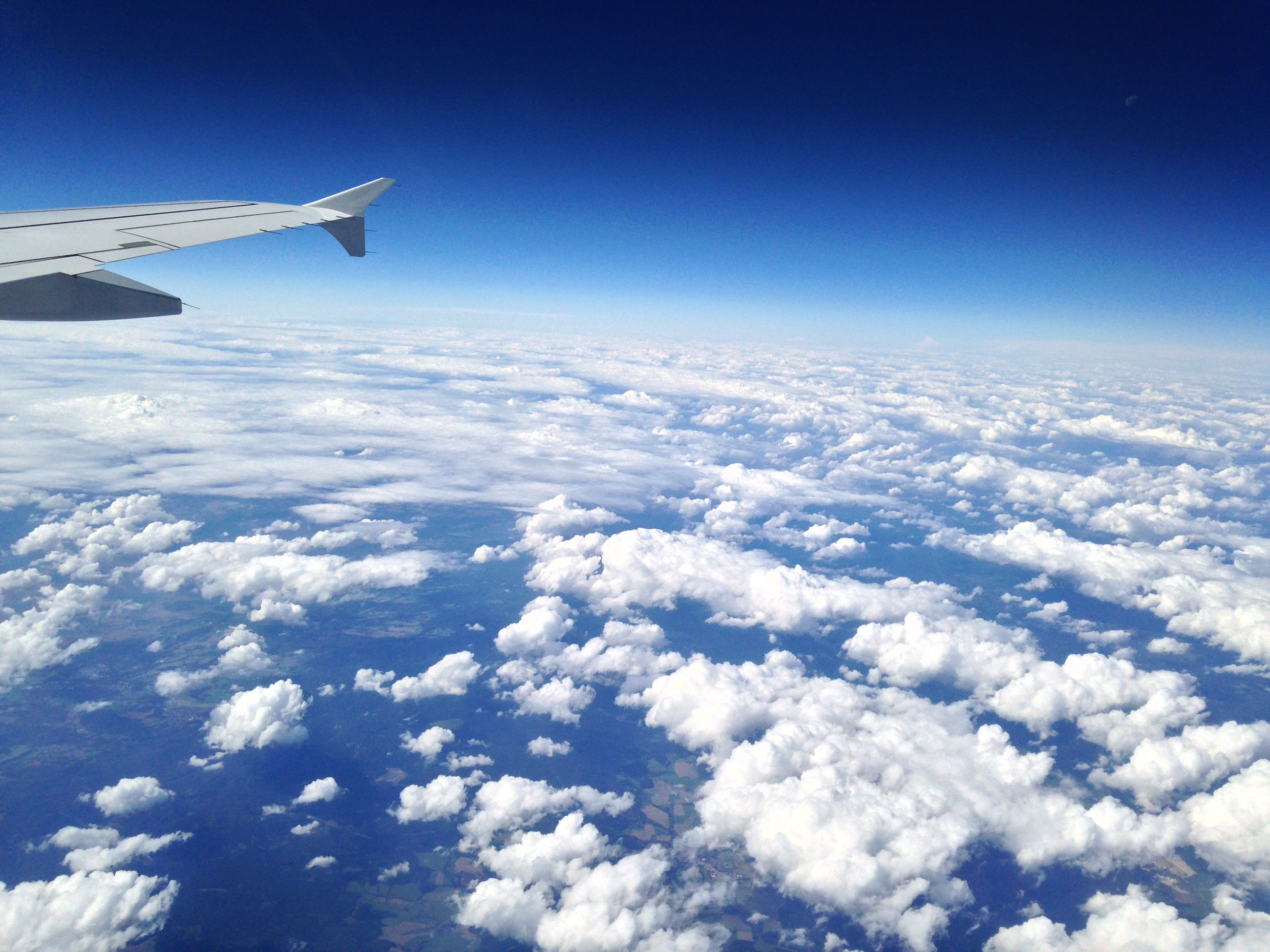 flying, airplane, air vehicle, aircraft wing, aerial view, blue, transportation, mid-air, sky, part of, landscape, beauty in nature, scenics, mode of transport, cropped, nature, cloud - sky, travel, white color, cloudscape