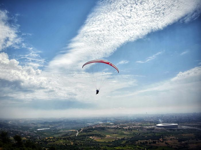 Person parachuting over landscape against sky