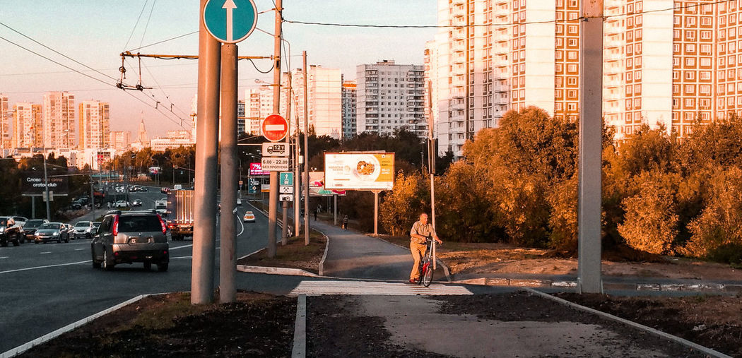 Moscow evening, an elderly man on his bike Moscow Bicyclist Appartment Block Appartment Building Russia Golden Hour Sidewalk Sunset Summer Skyscrapers City Road Land Vehicle Car Architecture Sky Building Exterior Built Structure Road Sign Traffic Stop Sign City Street Do Not Enter Sign Bicycle Lane