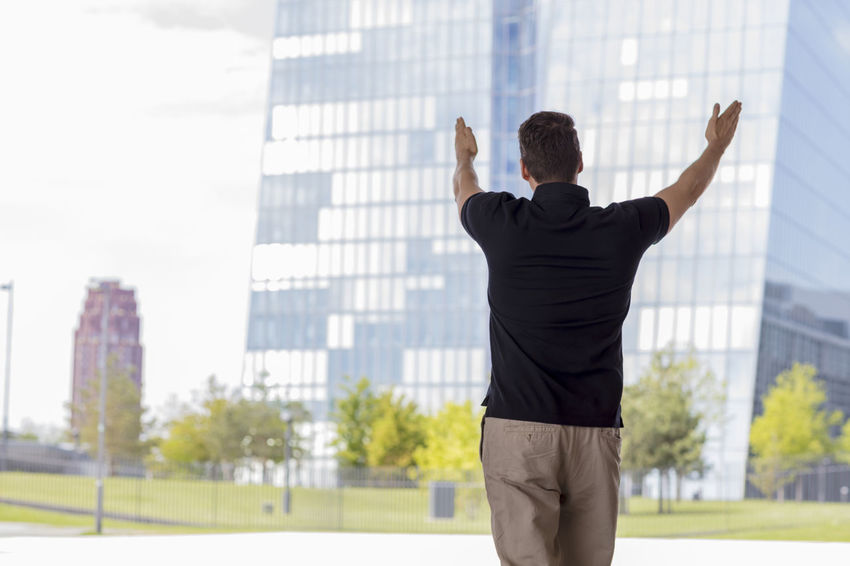 Casually dressed man, wearing khaki pants and a golf shirt raising hands and pointing towards Frankfurt office buildings. Medium shot. Back turned away from camera. Architecture Business City Khaki Pants Man Rear View Standing Sunny Back Turned Buildings Casual Clothing Caucasian Day Gesturing Glass Hand Gesture Handsome Medium Shot Model Office Building Pointing Pointing Fingers Summer Tall Urban