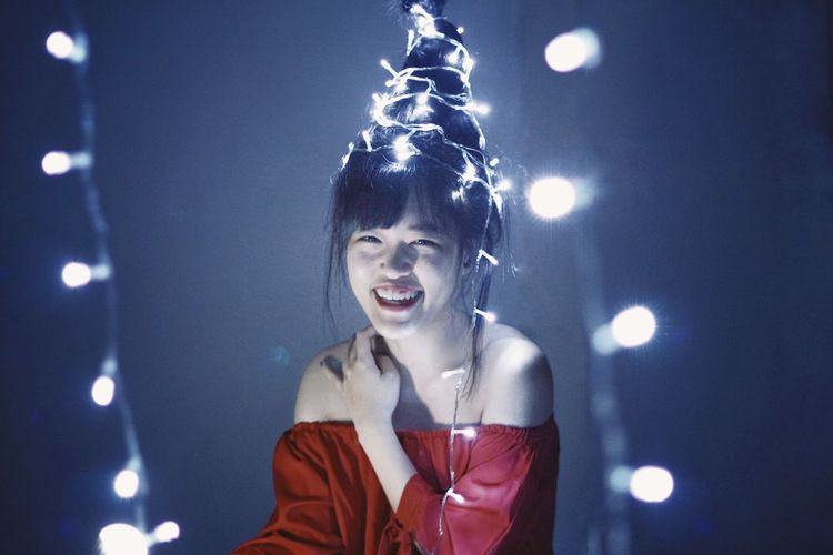 Portrait of woman and christmas tree hairstyles against illuminated light