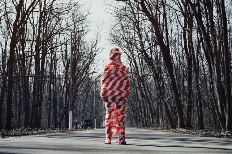 Woman wrapped in cordon tape standing by bare trees on road