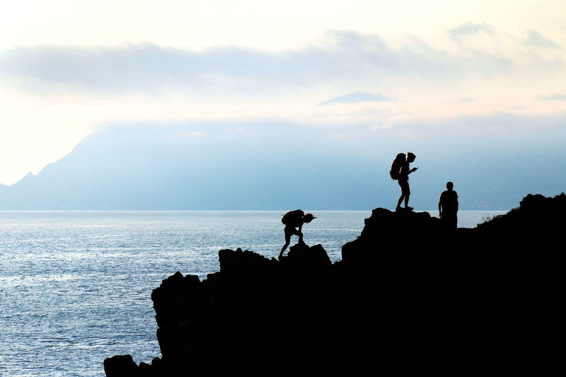 Hiking Sunset Silhouettes Activity Beauty In Nature Cloud - Sky Hiker Leisure Activity Lifestyles Men Mountain Nature Outdoors People Real People Rock Rock - Object Scenics - Nature Sea Silhouette Sky Standing Three People Tranquil Scene Water Women