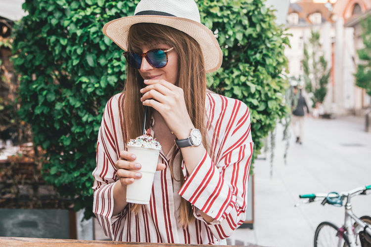 Young Woman in Beautiful Urban Scenery drinking a Milkshake Hat Drink One Person Real People Women Young Adult Lifestyles Leisure Activity Young Women Holding Food And Drink Adult Clothing Refreshment Drinking Coffee Sunglasses Coffee - Drink Glasses Front View Fashion Beautiful Woman Outdoors Hairstyle Fashion Blogger Watch Urban Urbanphotography City Ljubljana Slovenia Portrait Portrait Of A Woman Woman Casual Clothing Casual Look Milkshake