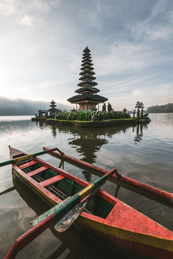 Empty red rowboat facing the floating shrine in Bedugul, Indonesia ASIA Asian Culture Asian Temple South East Asia Religion Belief Spirituality Built Structure Place Of Worship Sky No People Travel Travel Destinations Shrine Outdoors Boat Water Temple INDONESIA Bali Balinese Culture Floating Island Floating Shrine Shrine Lake Blue Sky And Clouds Morning Light Peaceful Travel Photography Rowboat EyeEmNewHere Capture Tomorrow