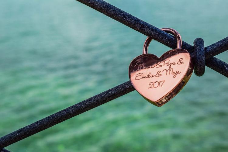 Close-up of padlocks hanging on railing against river