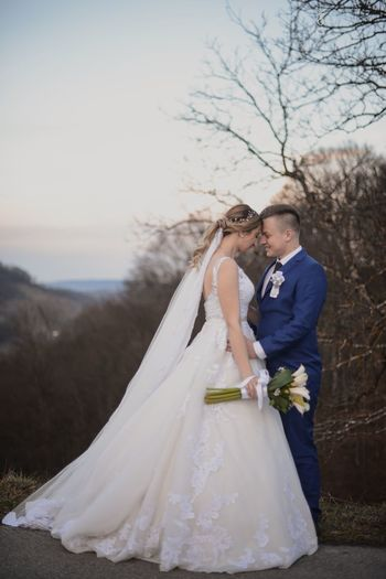 Bride holding flower bouquet with groom embracing against sky