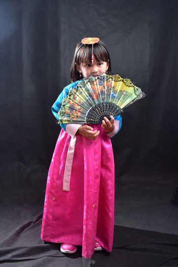 Cute girl in traditional clothing holding hand fan